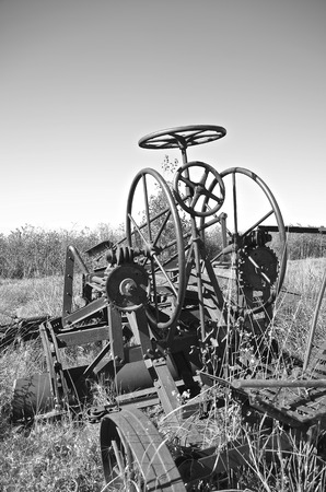 grader: A very old vintage road grader with many gears and wheels for controlling the blade is left in a salvage and junkyard.