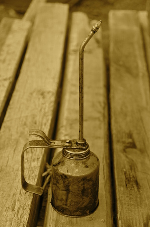 lubricate: Long stemmed oil can rests on a wood work bench. sepia