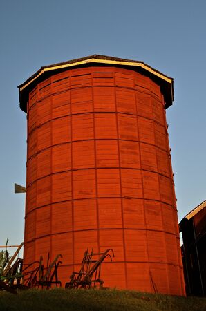 Old wood restored silo with horse drawn plows at the base in the early morning sunrise