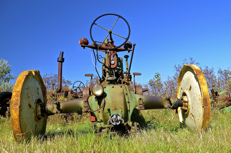 old tractor: An old tractor is missing the rear tires and seat. Stock Photo