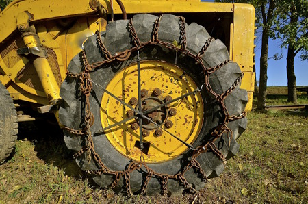 traction: Chains for greater traction are placed around the circumference of a huge industrial tractor.