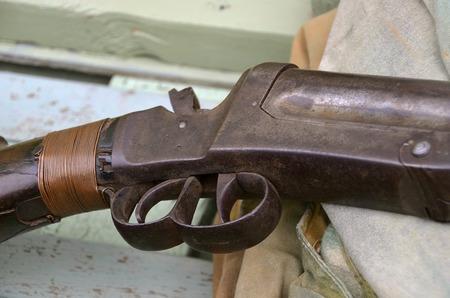 A vintage double barrel .12 gauge shotgun rest in the bottom of a duck boat.