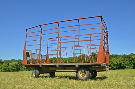 caged: A caged box is parked in a hay field where it receives the bales from a bale thrower. Stock Photo