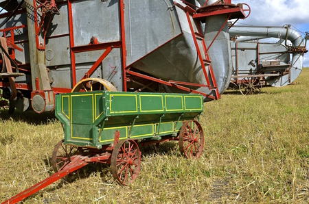 hitch: An old wagon box on rusty steel wheels and long hitch is parked in the stubble of a wheat field for hauling from the threshing of the machines.