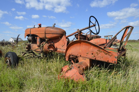 corrosion: Orange tractor in the long grass without rear wheels