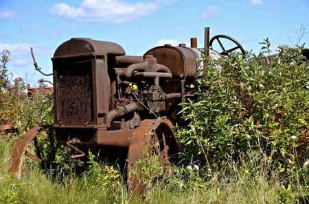 lugs: Very old rusty tractor left in the bushes