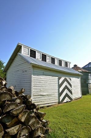 An old wood shed with white siding has vents to allow moisture escape from the drying wood stored inside