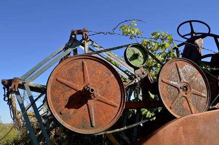 propelled: The rusty header of an old fashioned self propelled combine is decorated with weeds and vines. Stock Photo