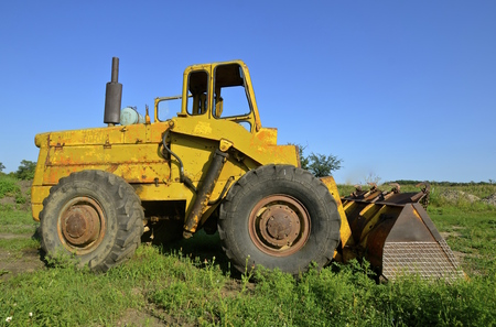 mover: Standing in a filed is a vintage earth mover with a large bucket for loading. Stock Photo