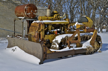 junked: Parked in the snow is an old junked bulldozer with a hydraulic blade. Stock Photo