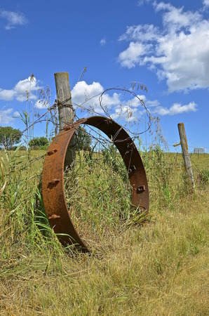 traction engine: An old industrial steel rusty wheel leans against a weathered fence post.