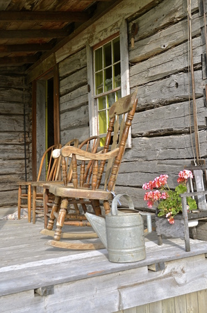 An overhang of a log cabin provides porch space for a rocking chair.