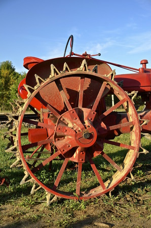 traction: Heavy old steel wheel of a tractor with metal lugs for traction.