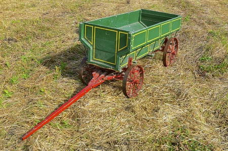shocks: An old green grain wagon with steel wheels is parked in the stubble and straw of a wheat field
