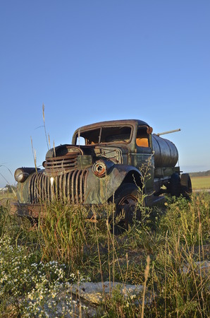 wornout: Parked in the long grass and weeds is an old worn-out water truck with a broken windshield Stock Photo