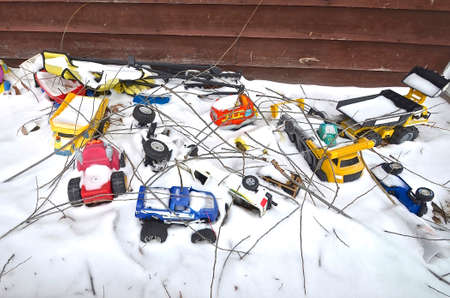 Toys left in a sandbox are covered with snow and twigs from winter winds.
