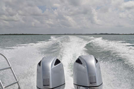 twin engine: Huge twin engine outboard boat motors leave a huge wake  in the Caribbean Sea