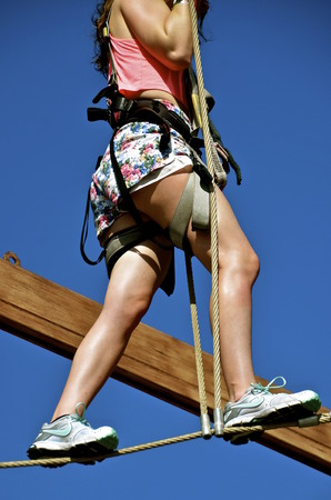 A young girl walks across a tight rope in an aerial obstacle course. Banco de Imagens