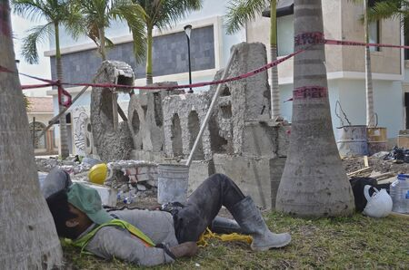 cozumel: A construction worker naps on a job site of creating a cement COZUMEL sign on the island. Stock Photo
