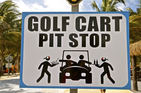 maneuvering: A unique Mexican sign in a resort area indicating food and beverages are available while maneuvering a golf cart on the streets. Stock Photo