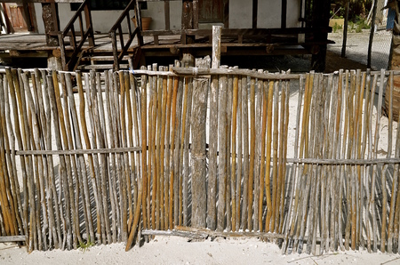 keepout: A front yard fence is made of sticks and poles in front of a home in a Mexican residence