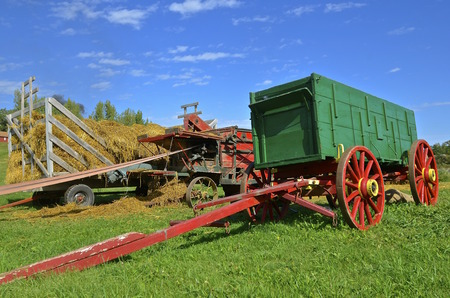 shocks: An old green wagon with a long hitch is used to haul grain from threshing.