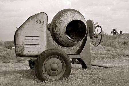 motorizado: An old pull motorized cement mixer at an industrial construction site. Foto de archivo