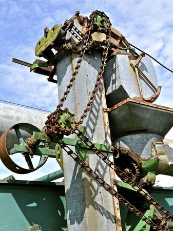 poleas: Los engranajes, cadenas, ruedas dentadas y poleas del ascensor de una m�quina trilladora de edad. Foto de archivo
