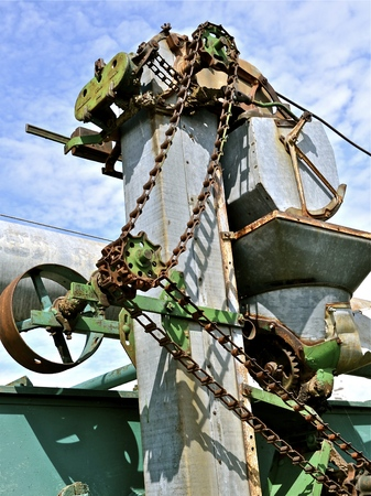 poleas: The gears, chains, sprockets, and pulleys of the elevator of an old threshing machine. Foto de archivo