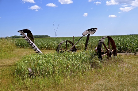 afield: Long grass in afield grows around an antique old hay mower with an extended sickle bar. Stock Photo