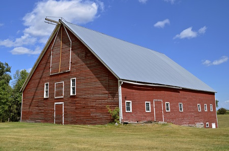 old red barn: A n old red barn with a hay loft has a new steel roof. Stock Photo