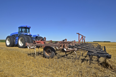 cultivator: A large modern tractor pulling a field cultivator in the stubble of a wheat field.