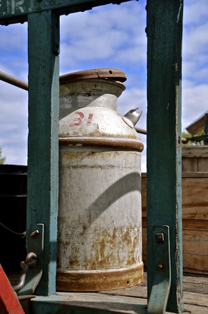 identifying: An old 10 gallon milk can  with rusty and an identifying number printed in red