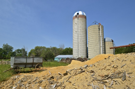 flanked: An old steel grain wagon with steel wheels, parked by a pile of sawdust, is flanked by three silos.