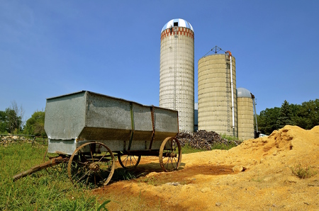 An old steel grain wagon with steel wheels, parked by a pile of sawdust, is flanked by three silos.