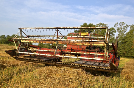 propelled: An old self propelled swather is parked a wheat field.