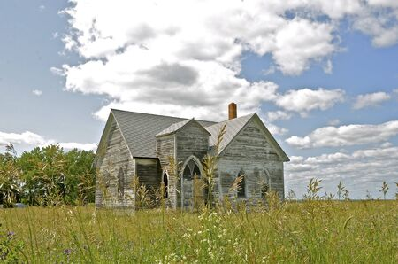 forlorn: An old white country church stands in the prairie grass, forlorn, abandoned, and neglected.