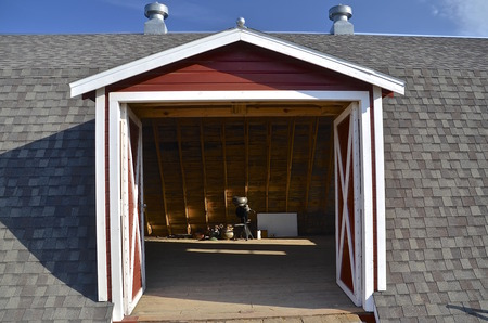 separator: Drive in entrance to a hay loft of a barn through a gable at the roofline exposes an old cream separator in storage