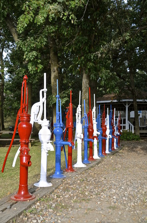 priming: Row of red, white, and blue hand pumps along a path.
