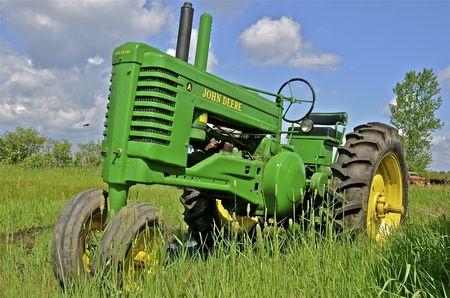 deere: BARNESVILLE, MINNESOTA- June 2, 2014; An old A stands in the long grass which is a product of John Deere Co, an American corporation that manufactures agricultural, construction, forestry machinery, diesel engines, and drivetrains