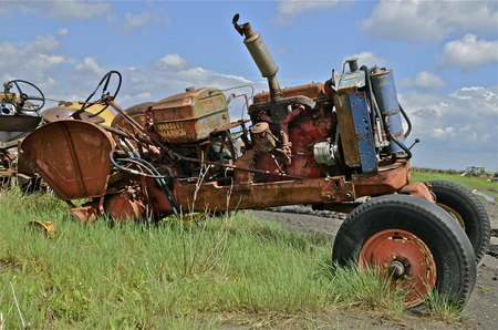 junked: Orange junked tractor without rear wheels and hood