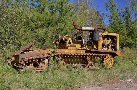 An old rusty logging machine on tracks resembles a bulldozer but used to move logs.