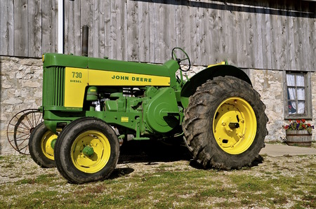 DOOR COUNTY, WISCONSIN, Oct oder 6, 2015:  An old John Deere 730 R diesel tractor is a product of John Deere Co, an American corporation that manufactures agricultural, construction, forestry machinery, diesel engines, and drivetrains.