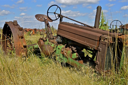 lugs: An old rusty tractor with with lugs on the wheels and no front rims.