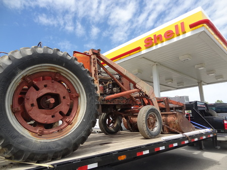 front end loader: GRAND FORKS, NORTH DAKOTA-June 20, 2013: An old Farmall tractor on a flatbed is parked in front of a Shell gas s, a subsidiary of Royal Dutch Shell.