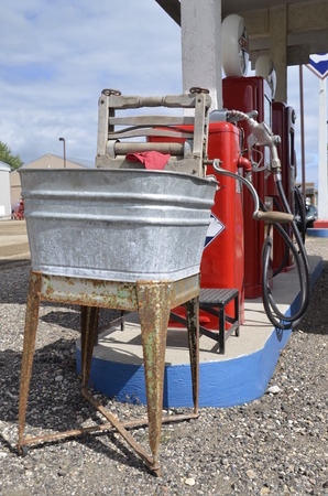 wash tub: Under a gas station canopy is a rusty stand with a galvanized wash tub for washing car windows.