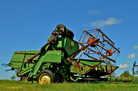 deere: BARNESVILLE, MINNESOTA- June 2, 2014; An old combine with a huge header and wheel is a product of John Deere Co, an American corporation that manufactures agricultural, construction, forestry machinery, diesel engines, and drivetrains. Editorial