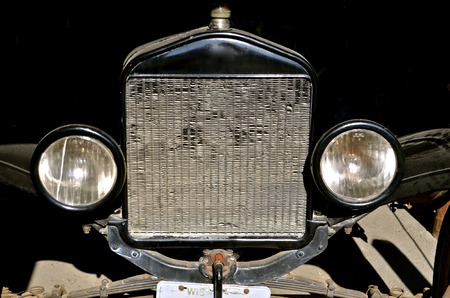 car grill: Grill, radiator, and headlamps of an old vintage car parked in a garage Stock Photo