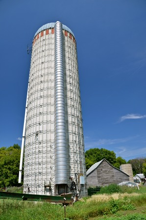 overwhelming: An abandoned large old silo rises into the sky overwhelming the weathered distant building in the background