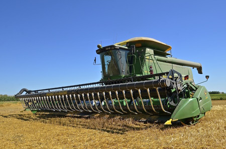 deere: MAYVILLE, NORTH DAKOTA-August 19, 2015: A self propelled combine in a wheat harvest scene is a products of John Deere Co, an American corporation that manufactures agricultural, construction, forestry machinery, diesel engines, and drivetrains.